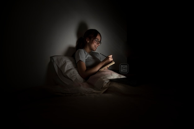 Donna che lavora fino a tardi a casa mentre a letto