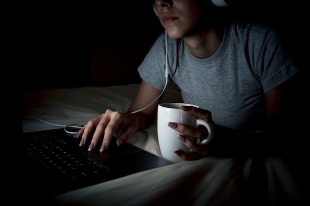 Donna che lavora fino a tardi sul computer portatile