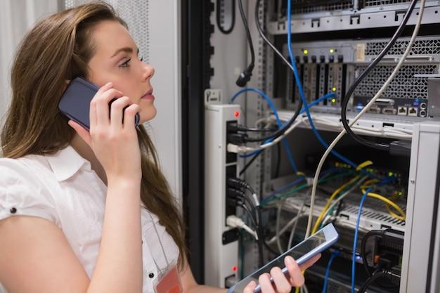 Donna che lavora su server con tablet pc al telefono