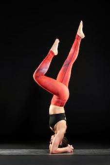 Donna che lavora su una stuoia di yoga facendo un headstand