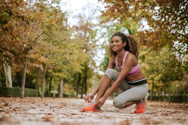 Donna che lega i lacci delle scarpe prima di correre, preparandosi per fare jogging nel parco.