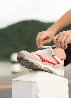 Donna che lega i lacci delle scarpe prima di iniziare a correre