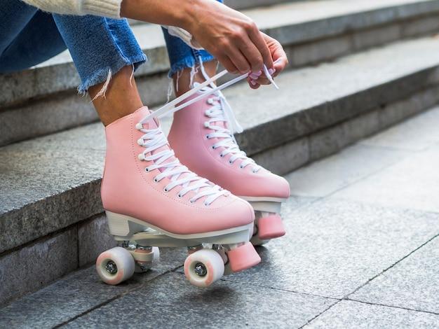 Donna che lega i lacci delle scarpe sui pattini di rullo con lo spazio della copia
