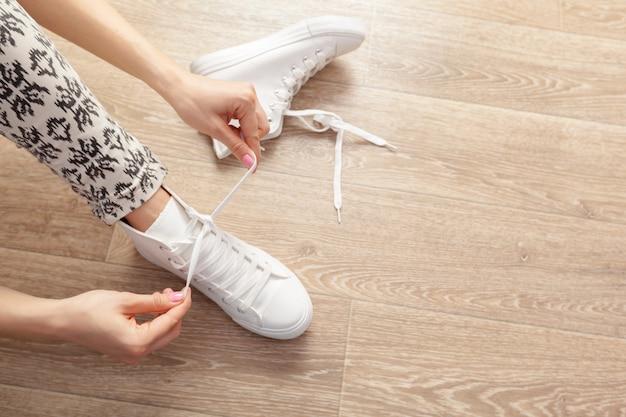 Donna che lega i lacci delle scarpe
