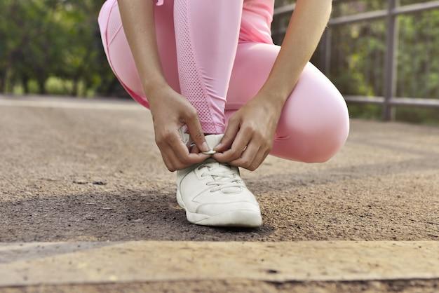 Donna che lega i suoi lacci delle scarpe. preparati per l'allenamento all'aperto