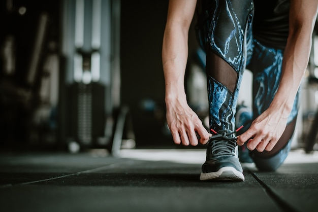 Donna che lega i suoi lacci delle scarpe prima dell'esercizio