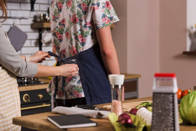Donna che lega il grembiule sull'uomo in cucina