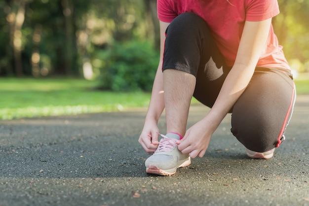 Donna che lega le sue scarpe sportive nel parco