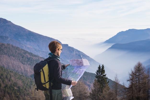Donna che legge la mappa trekking sulle alpi