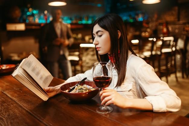 Donna che legge un libro al bancone del bar in legno