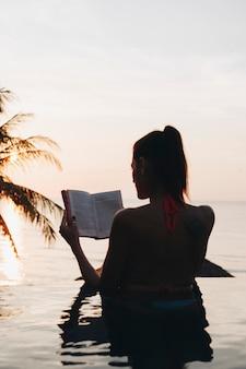 Donna che legge un libro in piscina
