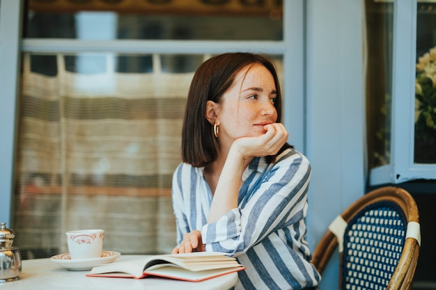 Donna che legge un libro in un caffè