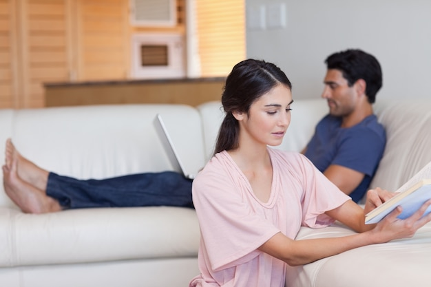 Donna che legge un libro mentre il suo fidanzato sta usando un computer portatile