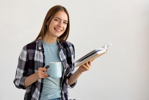 Donna che legge un libro mentre si tiene una tazza di caffè