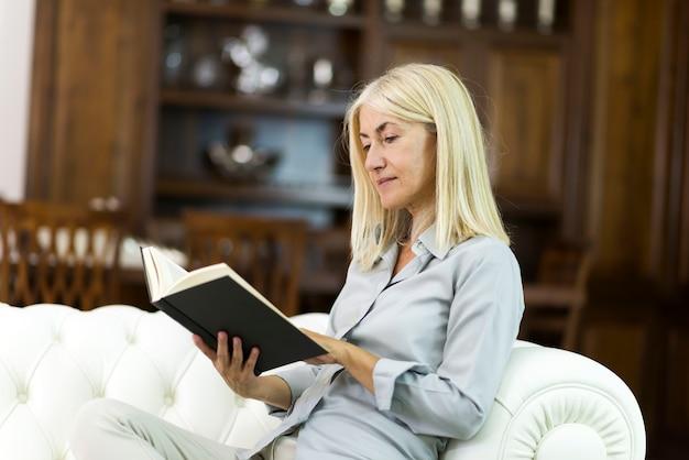 Donna che legge un libro nel suo salotto di casa