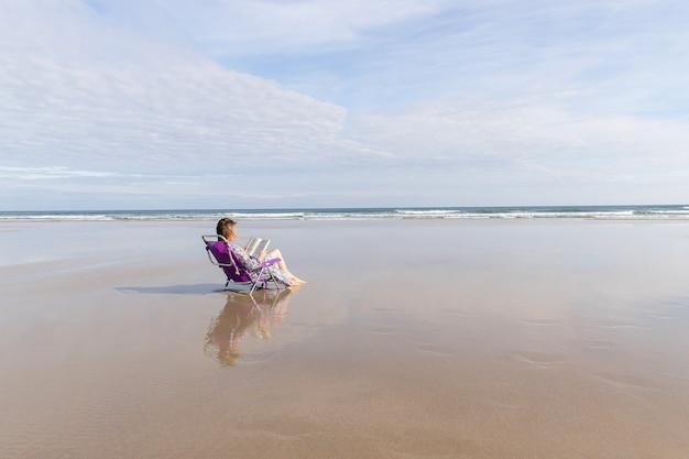 Donna che legge un libro seduto su una sedia sulla spiaggia