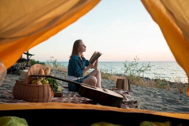 Donna che legge un libro sulla coperta da picnic