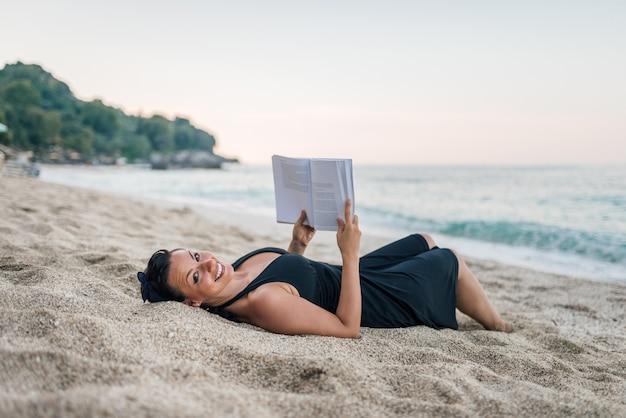 Donna che legge un libro sulla spiaggia. guardando la fotocamera