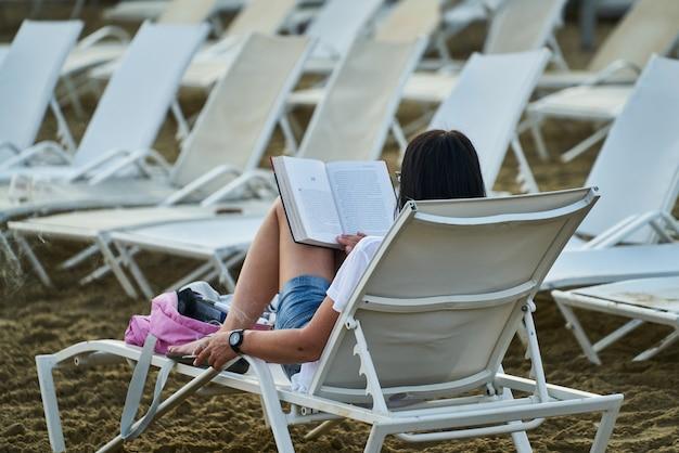 Donna che legge un libro sulla spiaggia