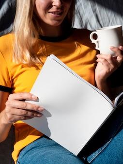 Donna che legge una rivista di mock-up