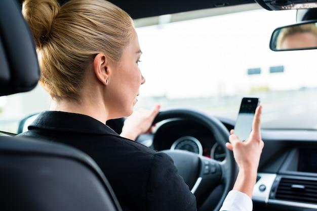 Donna che manda un sms sul suo telefono mentre guidando in macchina