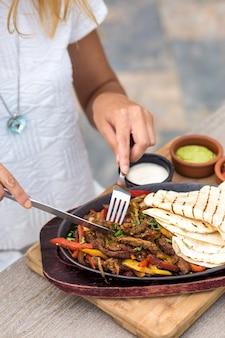 Donna che mangia agnello in padella con peperoni colorati, servito con focaccia