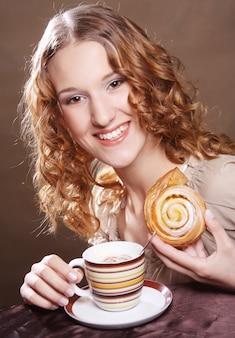 Donna che mangia biscotto e che beve caffè. foto da vicino