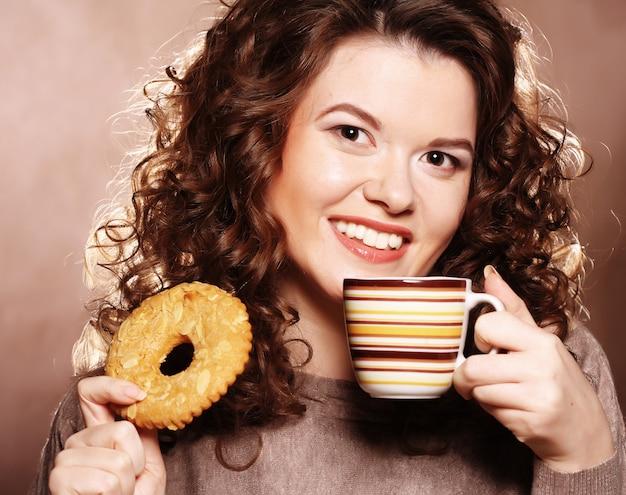 Donna che mangia biscotto e che beve caffè.