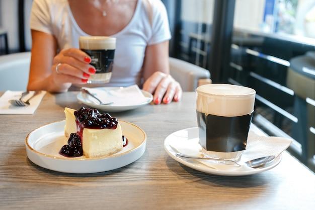Donna che mangia dolce e che beve caffè in una caffetteria.