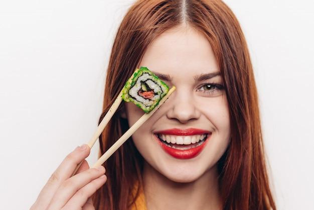 Donna che mangia i rotoli colorati con le bacchette di bambù, cibo asiatico, spazio leggero