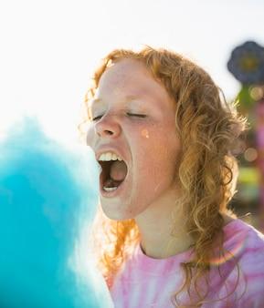 Donna che mangia il primo piano del filo di zucchero candito