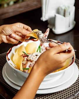 Donna che mangia insalata di carne in maionese con patatine fritte