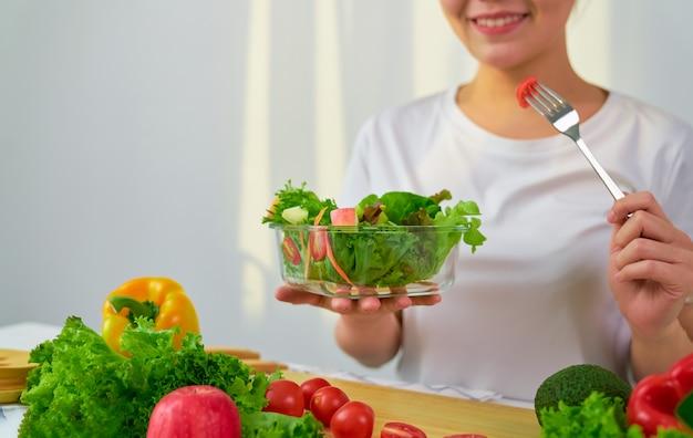 Donna che mangia insalata verde fresca a casa