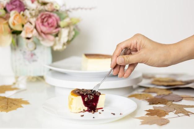 Donna che mangia la fetta di cheesecake con la forchetta.