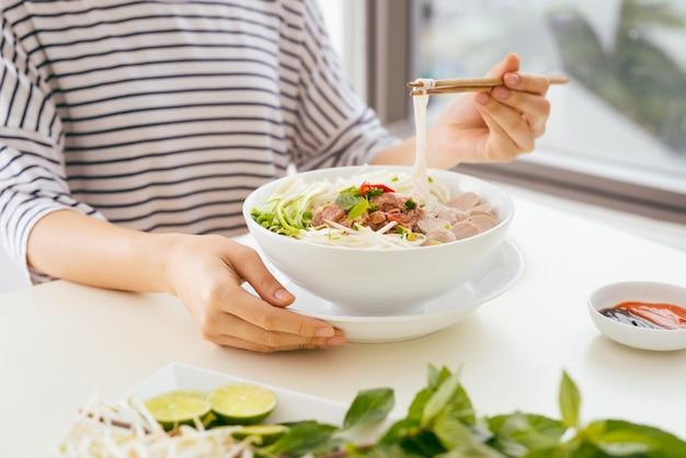 Donna che mangia la tagliatella vietnamita tradizionale di pho usando le bacchette.