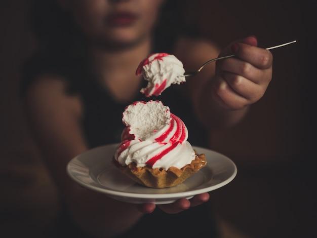 Donna che mangia la torta alla crema