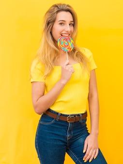 Donna che mangia lecca-lecca colorata