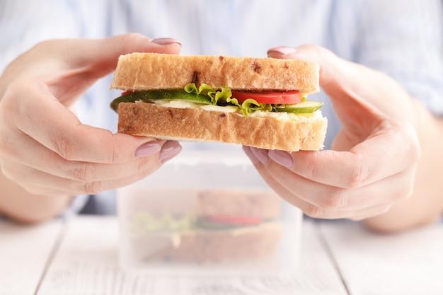 Donna che mangia panino salmone panini con pomodori e formaggio al lavoro