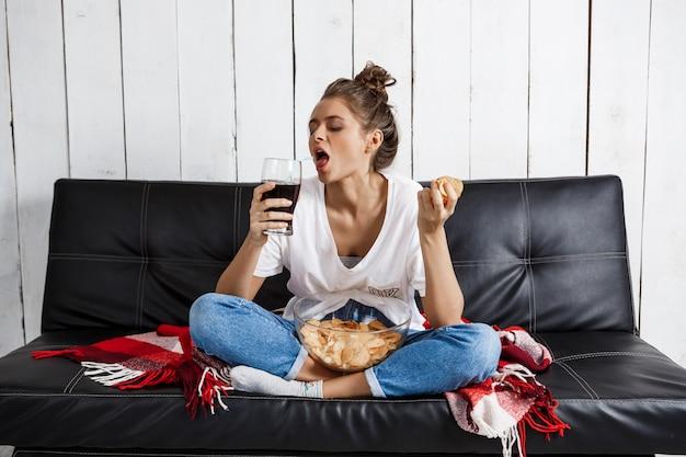 Donna che mangia patatine, bere soda, guardare la tv, seduto al divano.
