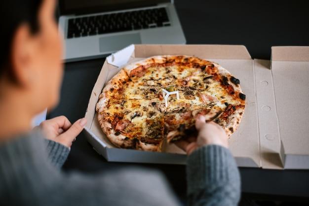 Donna che mangia pizza mentre lavora al computer portatile.