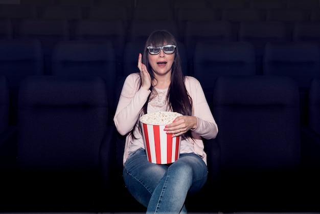 Donna che mangia popcorn al cinema