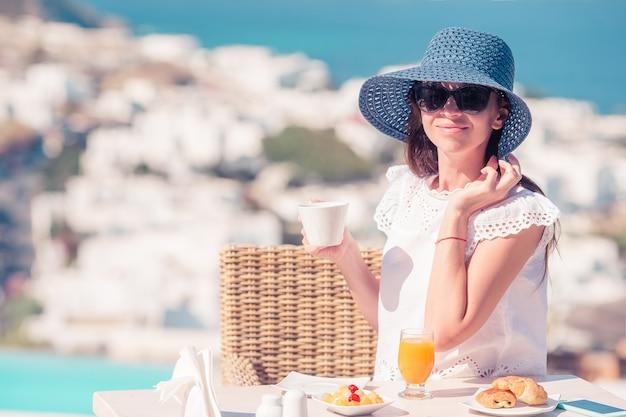 Donna che mangia prima colazione al caffè all'aperto con splendida vista sulla città di mykonos.