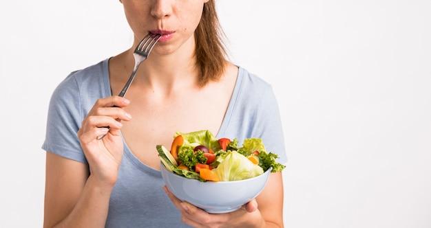 Donna che mangia un'insalata con una forchetta