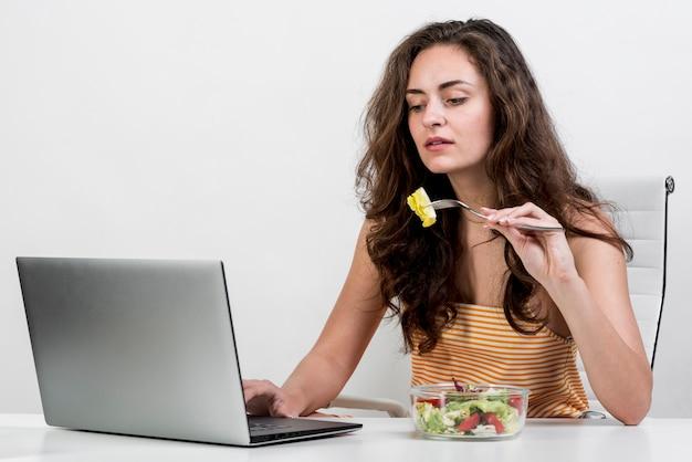 Donna che mangia un'insalata di lattuga