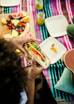 Donna che mangia un panino in spiaggia