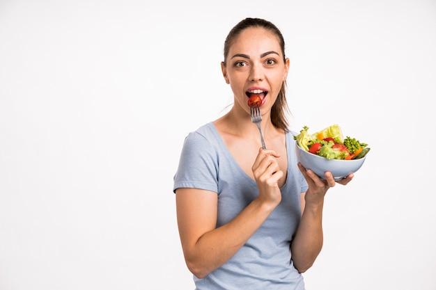 Donna che mangia un pomodoro con la forcella