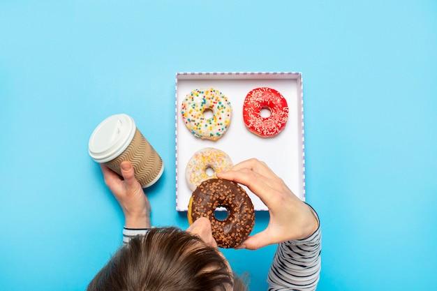 Donna che mangia una ciambella e che beve caffè su un blu. concept pasticceria, pasticceria, caffetteria.