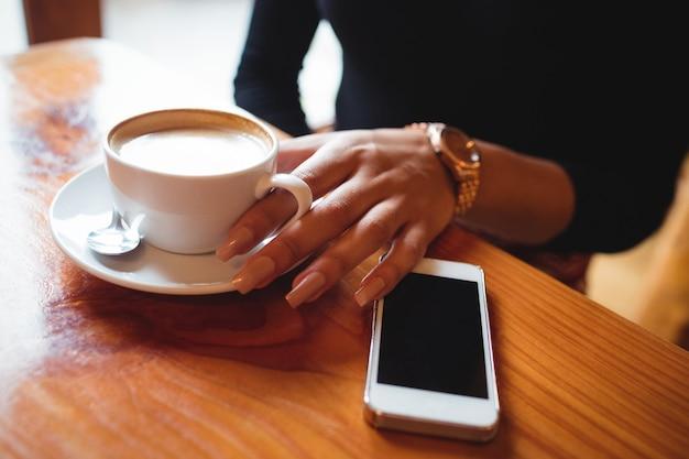 Donna che mangia una tazza di caffè in caffè