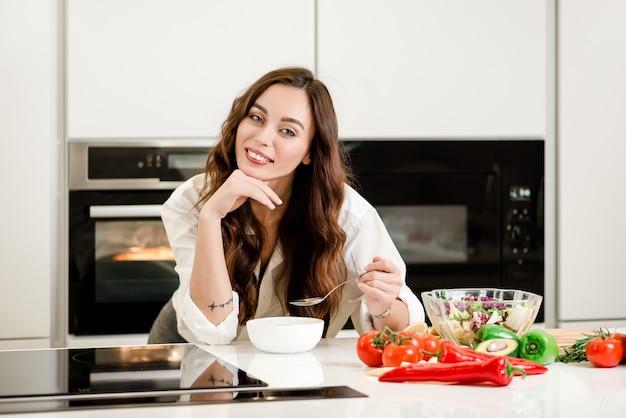 Donna che mangia una zuppa e verdure in una ciotola e sorridente sulla cucina