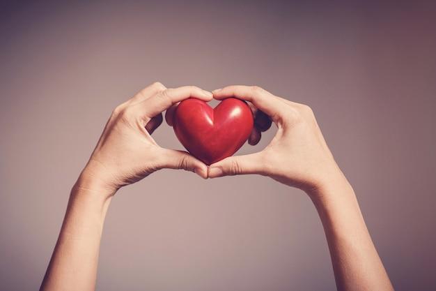 Donna che mantiene cuore rosso, assicurazione sanitaria, donazione, concetto di volontariato di beneficenza